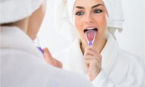 woman cleaning her tongue