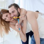 The couple is happy brushing their teeth together.