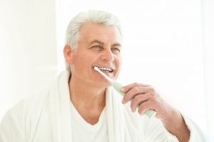 The senior brushes his teeth twice a day.