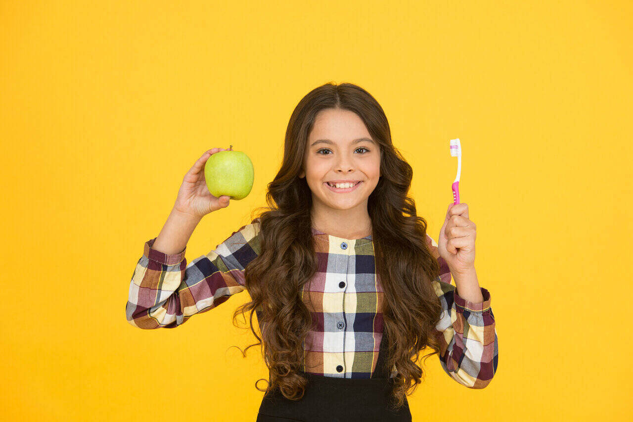 Holistic dental hygiene involves natural way of improving dental health. An example of this is munching an apple that can remove plaque.